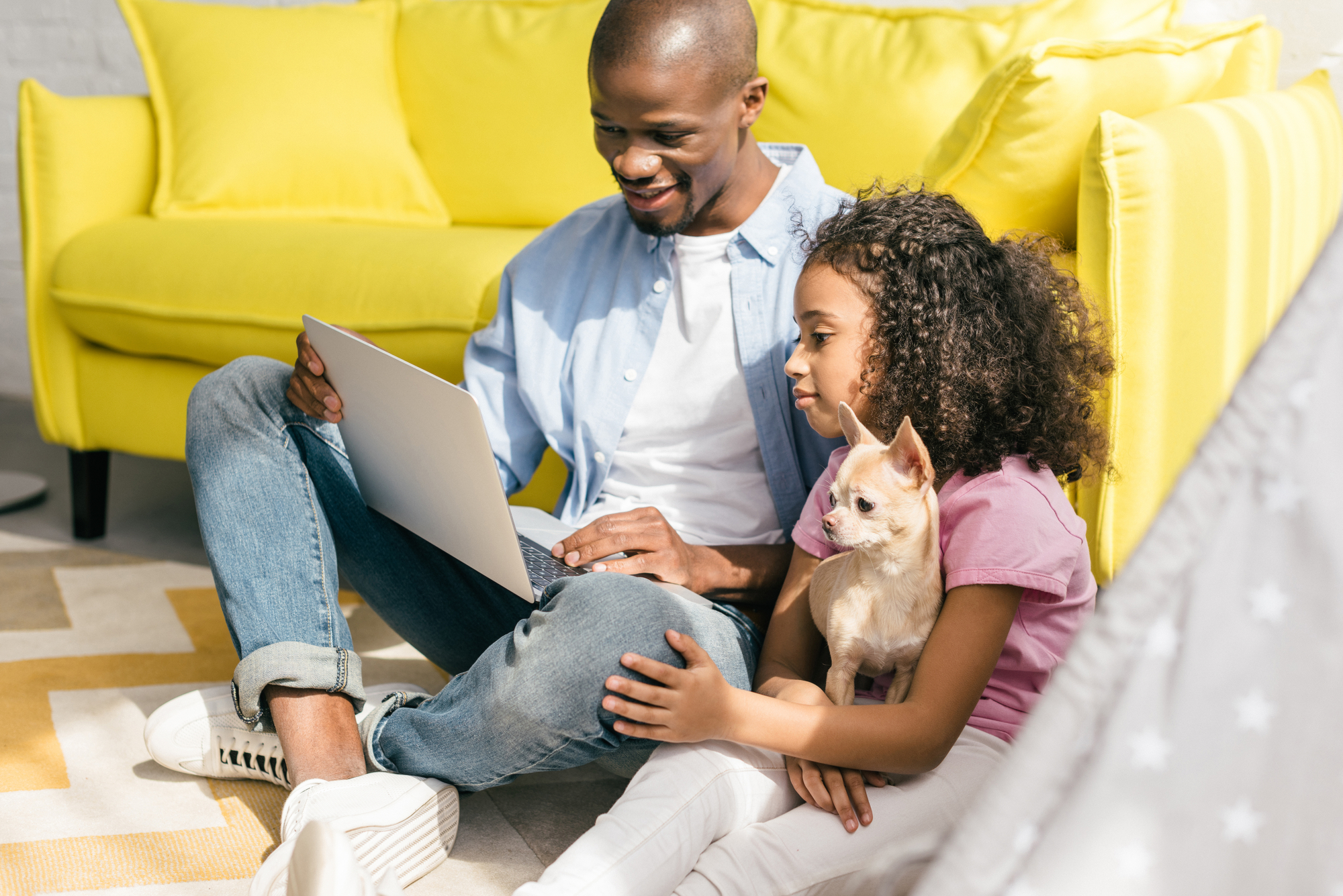 African american father and little daughter with dog using laptop together at home