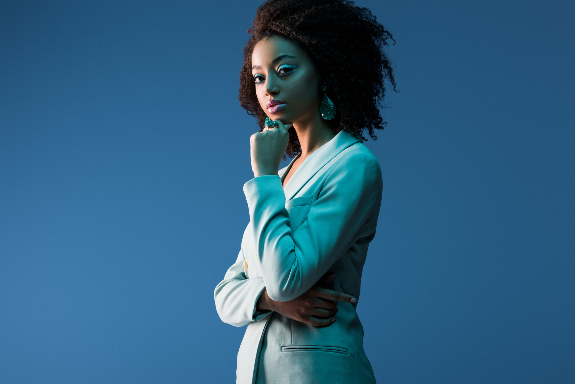 Attractive african american woman in suit isolated on blue