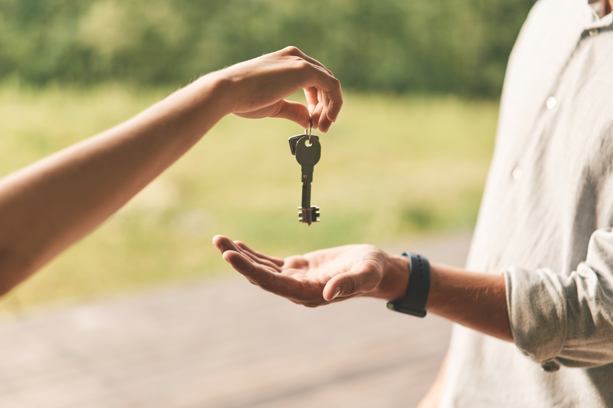 Close up of female real estate agent giving keys to man
