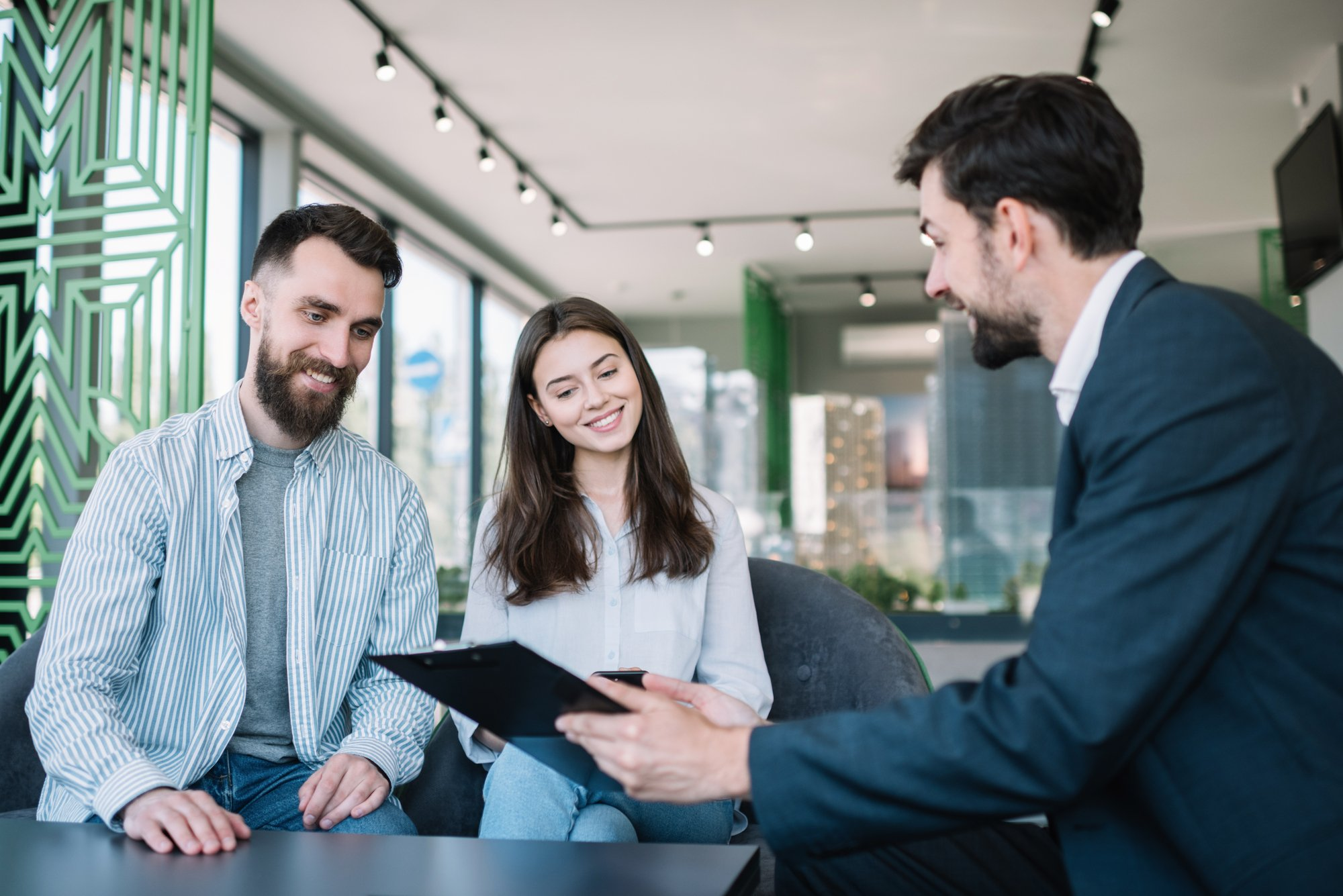 Happy young couple with smiling emotional faces choosing comfortable home in real estate agency. Buying house and property together. Financial advisor consulting partners in modern office