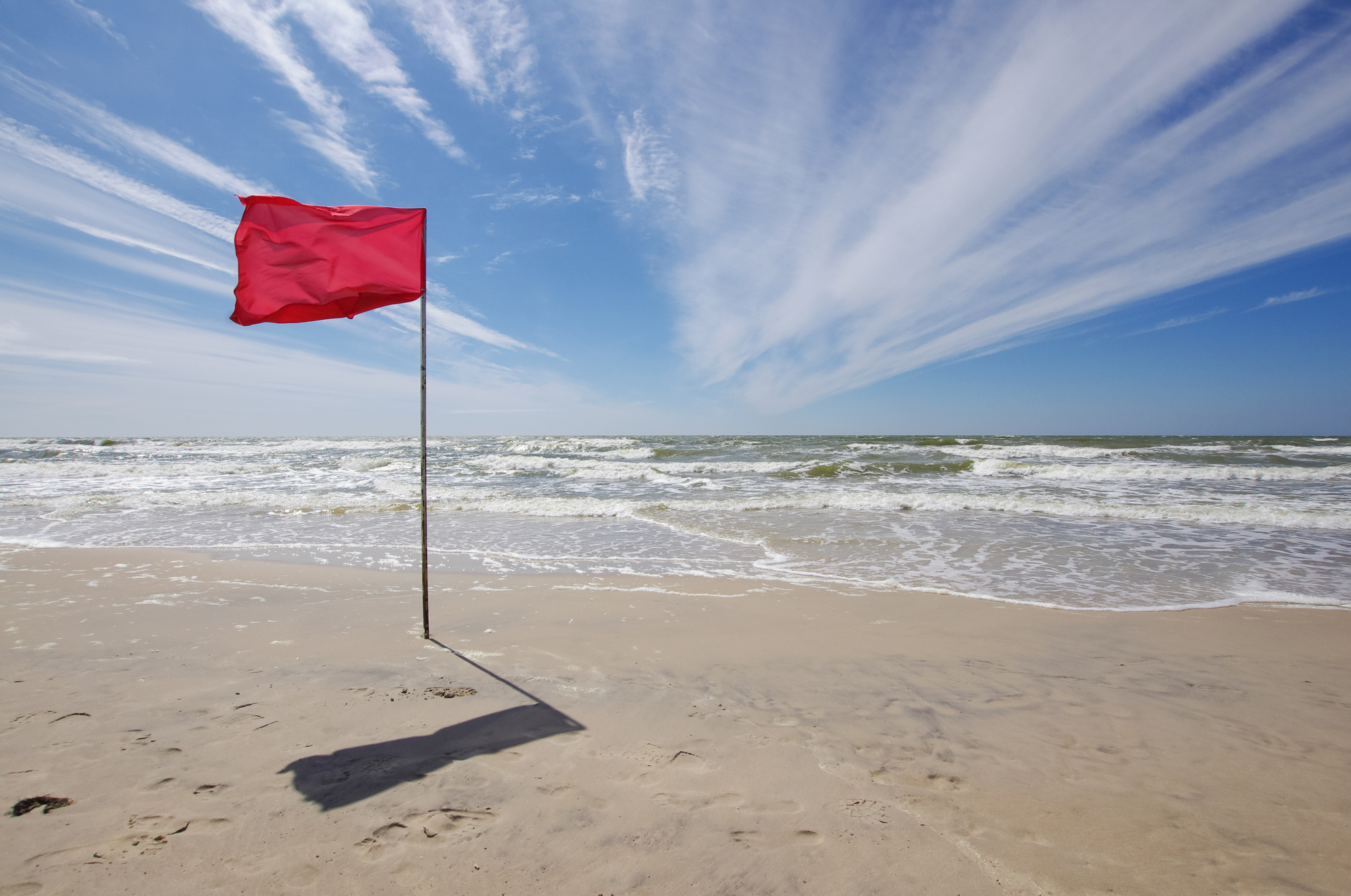 In the photo is captured red flag in the beach what means that beach bathing is prohibited