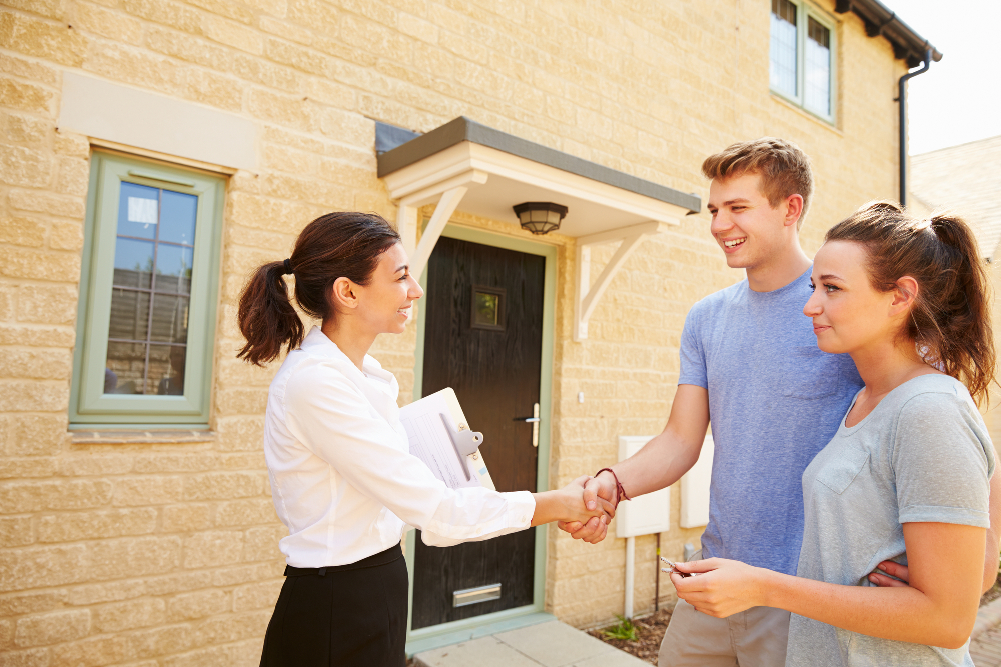 Real estate agent shaking hands with owners
