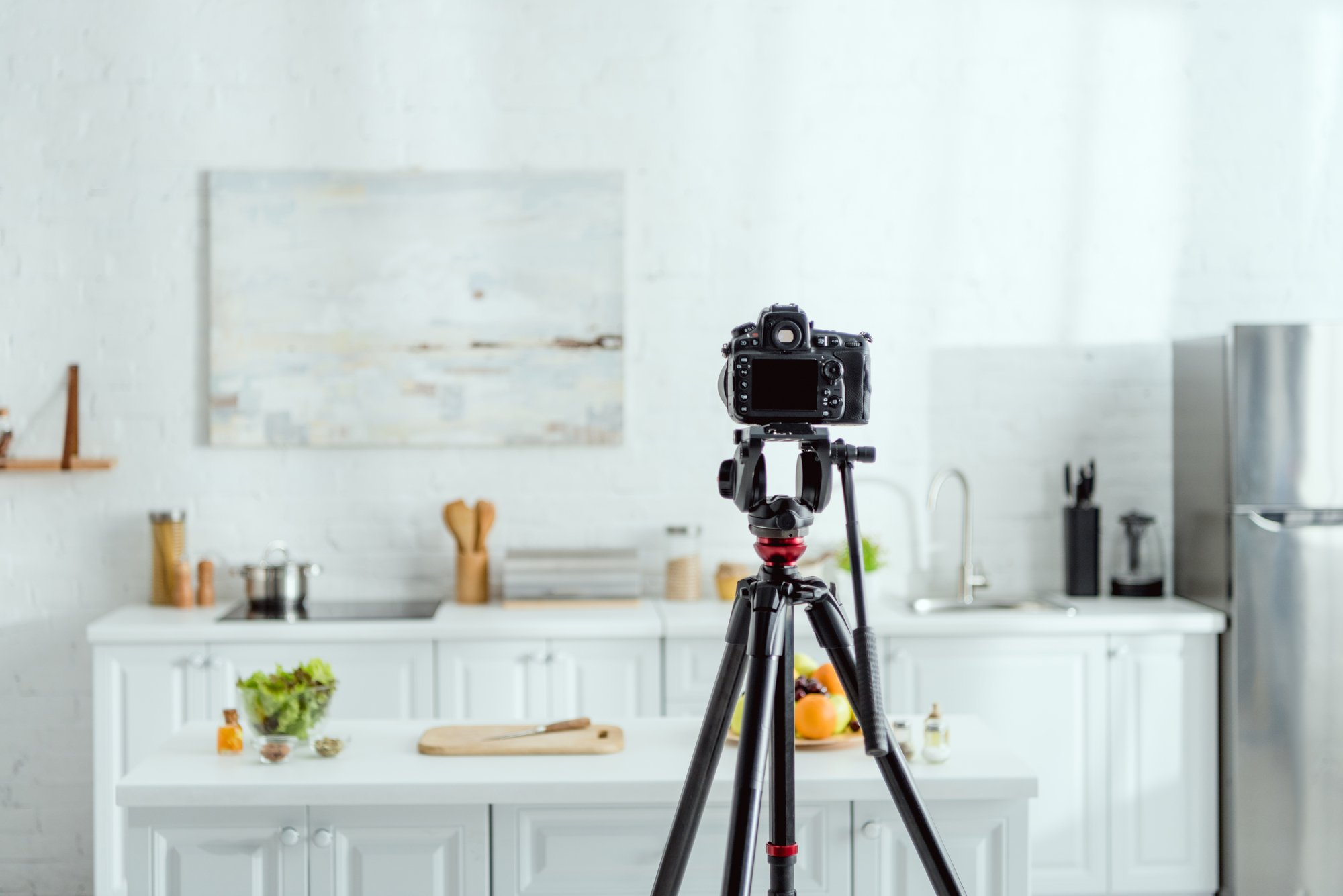 Selective focus of digital camera on tripod in modern kitchen